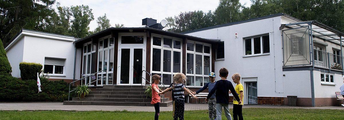 Außenansicht vom Eingang zum Schullandheim mit spielenden Kindern